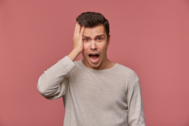 Young handsome shocked guy wears in checkered shirt, looks at the camera with wide open mouth in surprised expression, holds head, isolated over pink background.