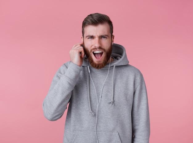 Молодой красивый поющий рыжий бородатый парень в серой толстовке с капюшоном слушает свою любимую песню в наушниках, наслаждается музыкой, выглядит счастливым, стоит на розовом фоне и подмигивает.