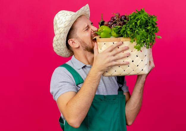 Молодой красивый славянский садовник в униформе и шляпе держит и кусает корзину с овощами