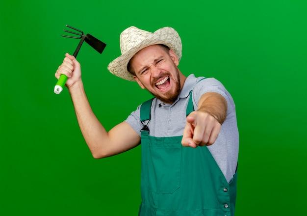 Молодой красивый славянский садовник в униформе и шляпе смотрит и показывает, держа грабли и кричит