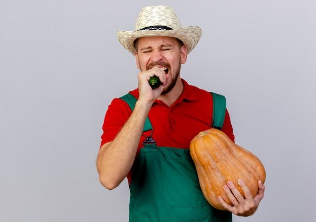 Giovane giardiniere slavo bello in uniforme e cappello che morde il cetriolo e che tiene la zucca butternut con gli occhi chiusi isolati