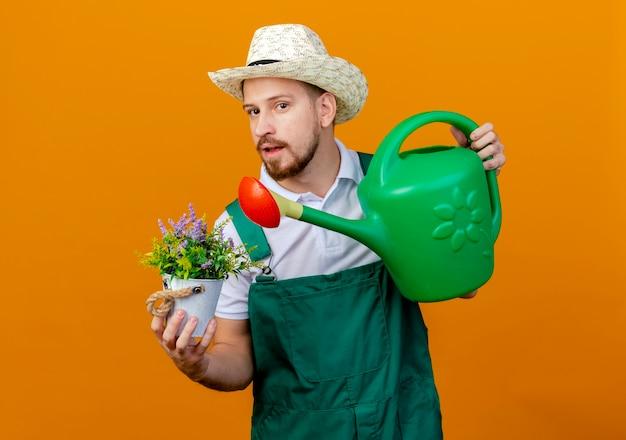 Giovane giardiniere slavo bello in uniforme e cappello che tiene vaso di fiori e annaffiatoio che sembrano isolati