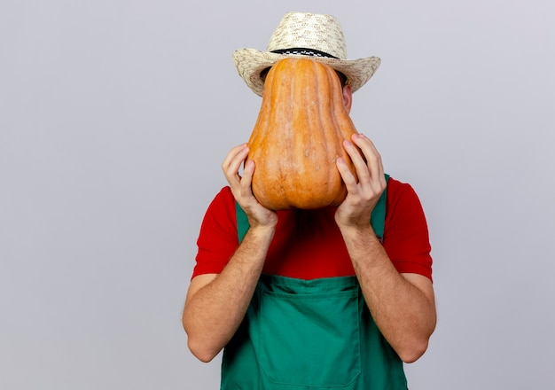 Giovane giardiniere slavo bello in uniforme e cappello che tiene e che si nasconde dietro la zucca butternut isolata