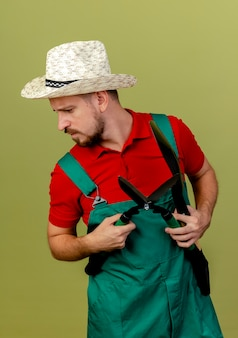 Young handsome slavic gardener in uniform and hat holding pruners turning head to side looking down