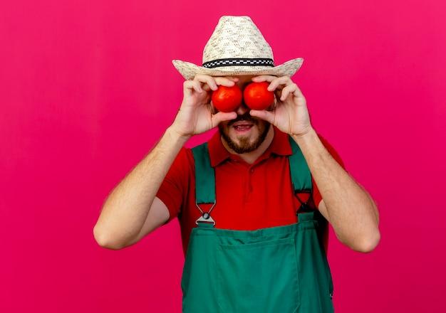 Giovane giardiniere slavo bello in uniforme e cappello che tiene i pomodori davanti agli occhi