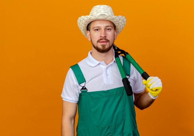Young handsome slavic gardener in uniform wearing hat and gardening gloves holding pruners on shoulder looking  isolated on orange wall with copy space