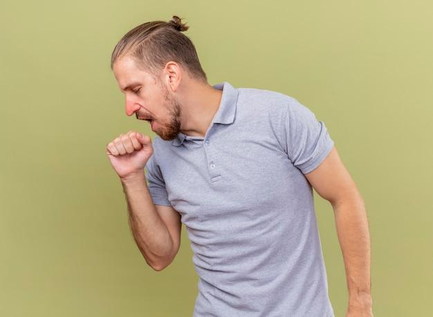 젊은 잘 생긴 슬라브 아픈 남자 복사 공간 올리브 녹색 배경에 고립 된 입 근처에 주먹을 유지 닫힌 눈으로 머리를 옆으로 기침