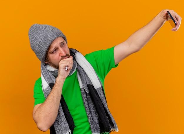冬の帽子とスカーフの咳を身に着けている若いハンサムなスラブの病気の男は、オレンジ色の背景で隔離されたselfieを取っている口に手を保ちます