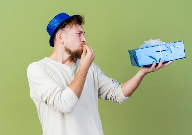 パーティー帽子をかぶって、オリーブグリーンの背景に分離されたキスジェスチャーをしているギフトボックスを見て若いハンサムなスラブ党の男