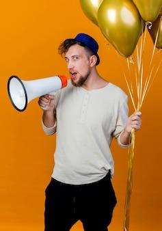 오렌지 배경에 고립 된 스피커로 이야기하는 카메라를보고 풍선을 들고 파티 모자를 쓰고 젊은 잘 생긴 슬라브 파티 남자