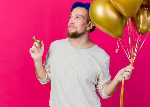Young handsome slavic party guy wearing party hat holding balloons and party blower looking at side isolated on pink wall