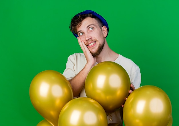 Young handsome slavic party guy wearing party hat standing behind balloons putting hand on face looking at side plunging into dreams isolated on green background