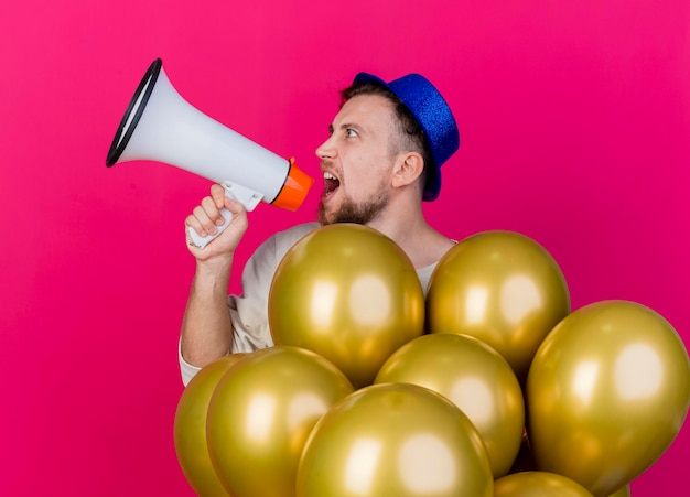 Young handsome slavic party guy wearing party hat standing behind balloons turning head to side shouting in loud speaker isolated on pink wall