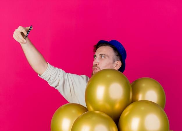 ピンクの壁に隔離されたselfieを取るキスジェスチャーをしている風船の後ろに立っているパーティーハットを身に着けている若いハンサムなスラブ党の男