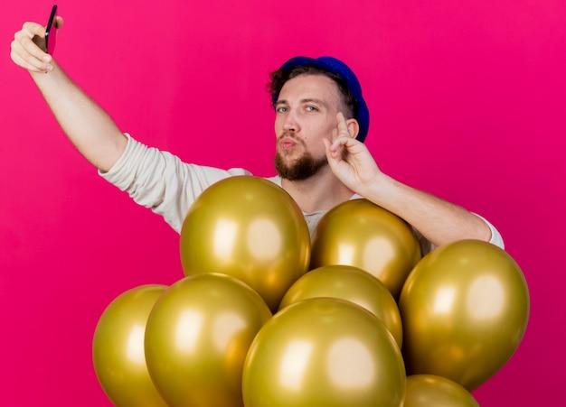 진홍색 배경에 고립 된 셀카 복용 얼굴을 만지고 카메라를보고 풍선 뒤에 서있는 파티 모자를 쓰고 젊은 잘 생긴 슬라브 파티 남자