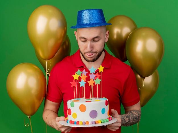 풍선을 들고 생일 케이크를보고 녹색 배경에 고립 된 혀를 보여주는 파티 모자를 쓰고 젊은 잘 생긴 슬라브 파티 남자