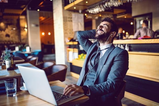 若いハンサムな笑みを浮かべてひげを生やした白人エレガントなビジネスマンのスーツでカフェに座っているとビデオ通話にラップトップを使用しています。耳にはイヤホンがあります。