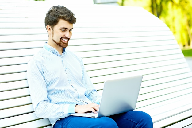 Young handsome smiling businessman model sitting on the park bench using laptop in casual hipster cloth