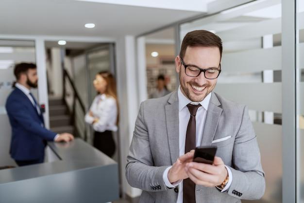 ホールに立っている間スマートフォンを使用して話しているスーツで若いハンサムな笑みを浮かべて白人実業家。バックグラウンドで彼の同僚は立ってチャットをしています。