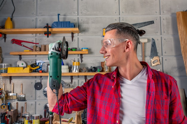 Young handsome smiling caucasian carpenter holding a circular saw in his hands in the workshop. ready to work