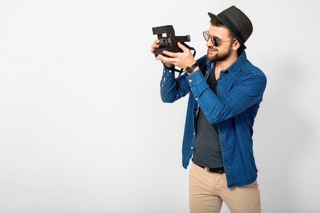 Young handsome smiling happy man holding vintage photo camera isolated on white studio background, wearing denim shirt, hat and sunglasses, photographer traveling and taking pictures