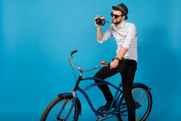 Young handsome smiling happy man traveling on hipster bicycle, holding vintage photo camera on blue studio background, wearing shirt, hat and sunglasses, photographer taking pictures