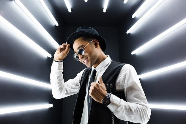 レトロなビンテージスタイルのスーツで若いハンサムな笑顔のヒップスター黒人男性がディスコナイトクラブでヒップホップを踊って楽しんでいます
