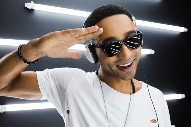 ヘッドフォンで音楽を聴き、ディスコナイトクラブでヒップホップスタイルで踊って、楽しんで、白い服を着た若いハンサムな笑顔のヒップスター黒人男性