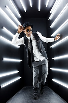 Young handsome smiling hipster black man in retro vintage style suit dancing hip hop in disco night club, having fun