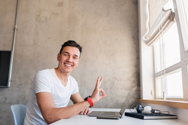 Young handsome smiling man in casual outfit sitting at table working on laptop, freelancer at home