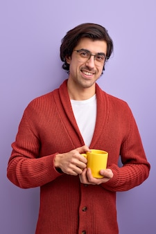 Young handsome smiling man drinking tea in morning, enjoy life
