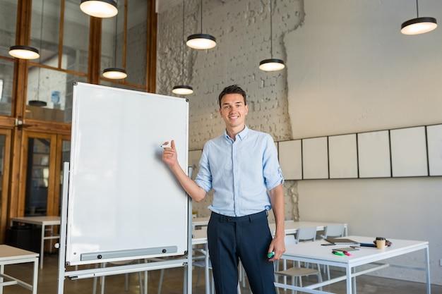 Молодой красивый улыбающийся человек, стоящий на пустой белой доске с маркером