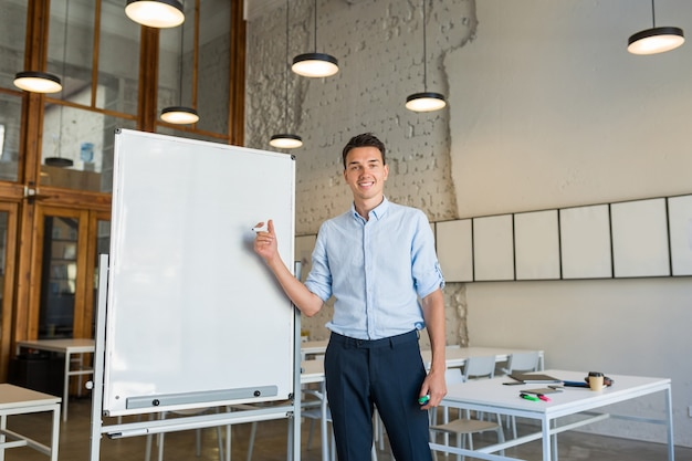 Young handsome smiling man standing at empty white board with marker