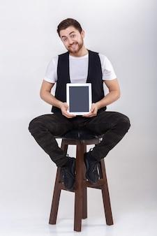 흰 셔츠에 수염을 기르고 태블릿을 들고 있는 검은색 조끼를 입고 회색 배경의 의자에 앉아 있는 젊고 잘생긴 미소 짓는 갈색 머리 남자
