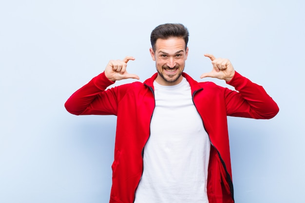 Young handsome sports man or monitor framing or outlining own smile with both hands, looking positive and happy, wellness concept against flat wall