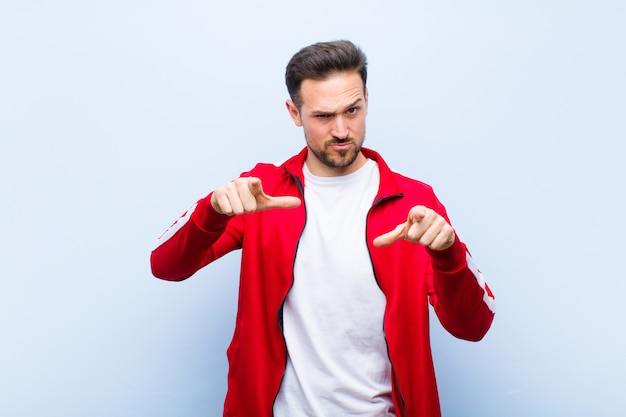 Young handsome sports man or monitor pointing forward at camera with both fingers and angry expression, telling you to do your duty on flat wall