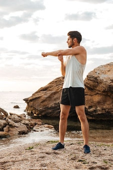 Young handsome sports man stretching hands before run at the beach