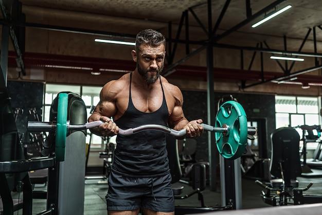 カメラ、腹部の筋肉、上腕二頭筋、上腕三頭筋の前でポーズをコーチングした後、理想的なボディを持つ若いハンサムなスポーツマンボディービルダー重量挙げ。スポーツウェア。