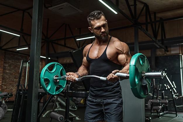 코칭 후 이상적인 몸을 가진 젊은 잘 생긴 스포츠맨 보디 빌딩 용기구 역도 카메라, 복부 근육, 팔뚝 삼두근 포즈. 운동복에.