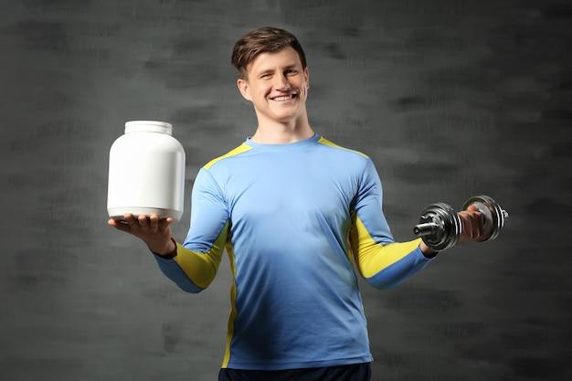 Молодой красивый спортсмен держит бутылку белка и гантели на черном
