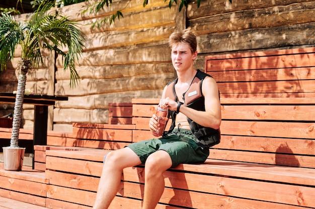 리조트의 화창한 날 벤치에 앉아 있는 동안 녹색 반바지와 안전 스포츠 재킷을 입은 젊고 잘생긴 스포츠맨