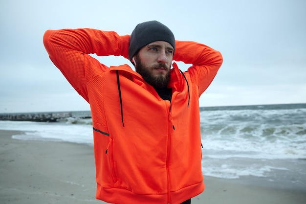Young handsome sporty bearded male with eyebrow piercing raising hands behind his head while looking pensively at sea view, frowning eyebrows and keepng lips folded