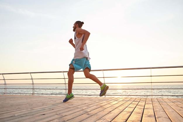 바다에서 아침 운동을하는 젊은 잘 생긴 스포티 한 수염 난 남자는 새벽에 아침 저깅을 즐깁니다.