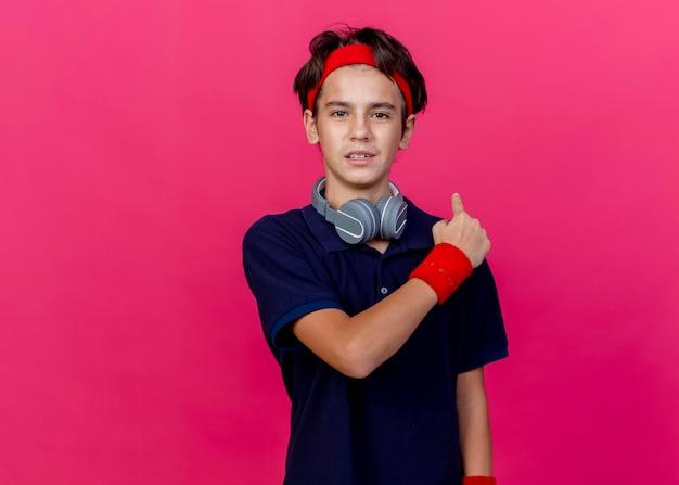복사 공간이 분홍색 벽에 고립 된 뒤에 가리키는 치과 교정기와 목에 머리띠와 팔찌와 헤드폰을 착용하는 젊은 잘 생긴 스포티 한 소년