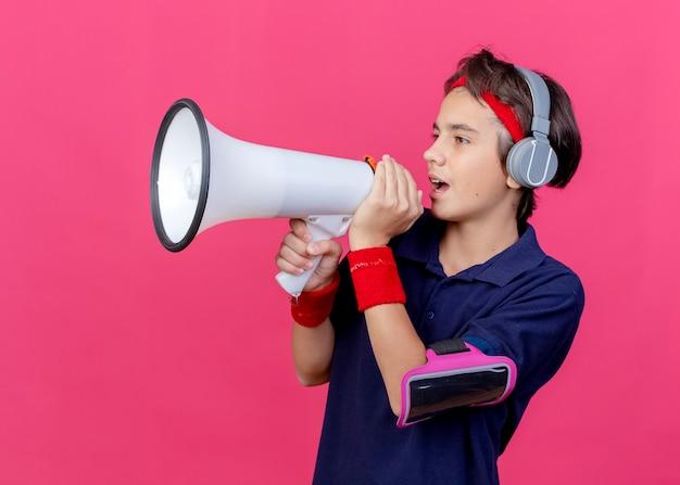 ヘッドバンドとリストバンドとヘッドホン電話アームバンドを身に着けている若いハンサムなスポーティな少年は、深紅色の壁に分離されたスピーカーでまっすぐに話している歯列矯正器を探しています