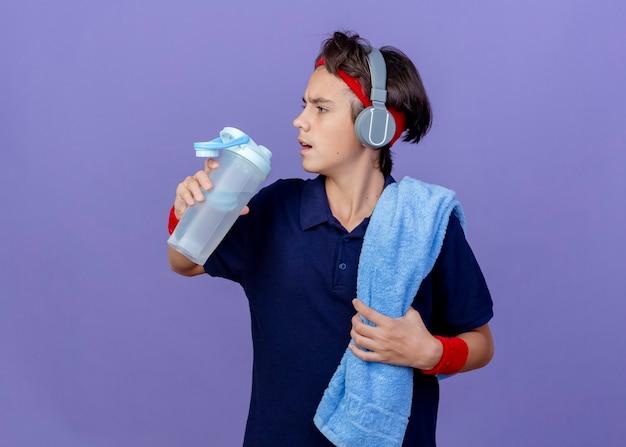 ヘッドバンドとリストバンドとヘッドフォンを身に着けている若いハンサムなスポーティな少年は、コピースペースのある紫色の壁で隔離された側を見て水筒を持って肩に歯列矯正器とタオルを持っています