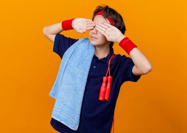 ヘッドバンドとリストバンドを身に着けている若いハンサムなスポーティな男の子は、オレンジ色の壁で隔離された目に手を保ちながら、肩に縄跳びが付いた歯列矯正器とタオルを着用しています