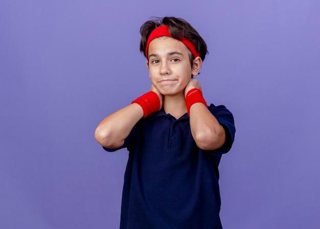 コピースペースで紫色の背景に分離されたカメラを見て首の後ろに手を保つ歯科用ブレース付きのヘッドバンドとリストバンドを身に着けている若いハンサムなスポーティな少年
