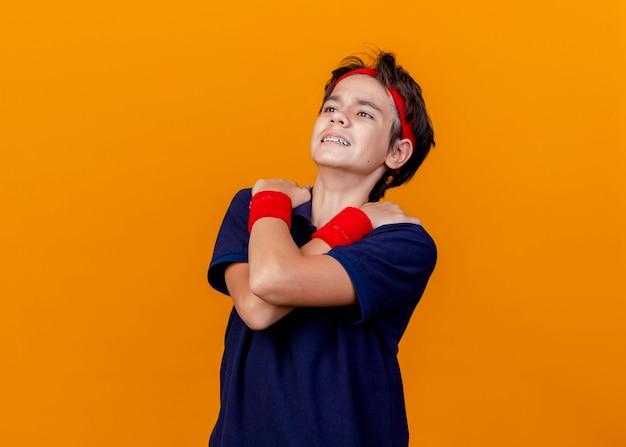 コピースペースでオレンジ色の背景に分離された肩に手を交差させてまっすぐに見える歯科用ブレース付きのヘッドバンドとリストバンドを身に着けている若いハンサムなスポーティな少年