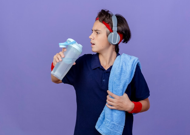Young handsome sporty boy wearing headband and wristbands and headphones with dental braces and towel on shoulder holding water bottle looking at side isolated on purple wall with copy space